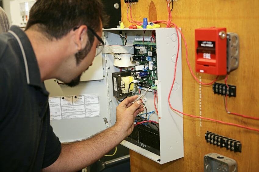 man maintaining fire alarm